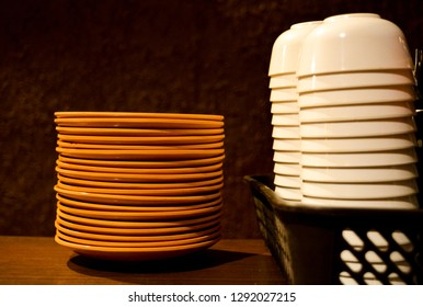 The image shows the set of brown coloured plates and white coloured bowls made of porcelain on a table.