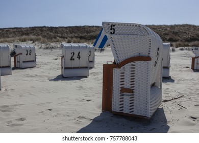 Image shows some beach chair without people in the sun