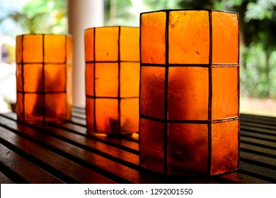 The image shows the sunlight effect on the three orange coloured glasses kept on a wooden table.
