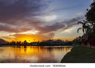 The image shows the sunset with clouds highlighted by the setting sun across the lake with the reflection of the sunset in the water