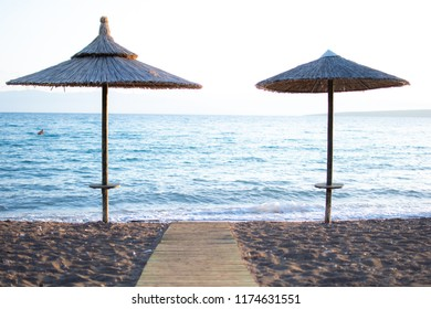 Image shows two umbrellas and a wooden path placed at a sandy beach.Summer concept.