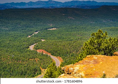 The image shows the view of the Arizona forest from the Mogollon Rim near Payson Arizona with a mountain range in the distance