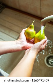 Image shows woman's hands washing pears under the water.