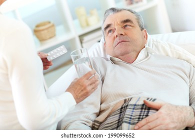 Image of sick senior man looking at his wife offering him to take pill