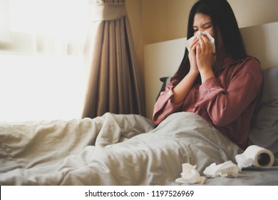 Image of sick woman in bed blowing her nose with white tissue paper and having more white tissue paper laying around with a roll of tissues. Gray bedsheets and blanket. Bedroom background.