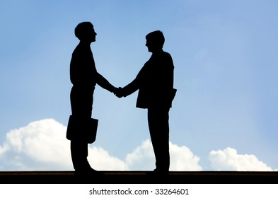 Image of silhouette business partners handshaking on a sky background