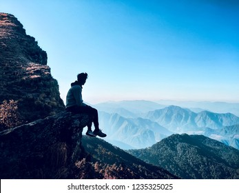 Image of silhouette of a solo traveller enjoying the beautiful panoramic view of rugged Himalayan mountains and the horizon while sitting on the edge of a cliff at the summit under clear blue sky.