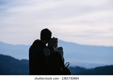 An image of silhouettes of young couple in love standing on the top of mountain