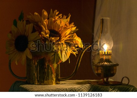 An image of silk sunflowers and ivy arranged in an antique brass watering can bathed in the golden light of an antique oil lamp.