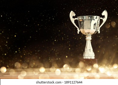 image of silver trophy over wooden table and dark background, with abstract shiny lights