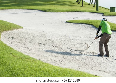 Image of a single male golfer in a sand trap swinging at a golf ball