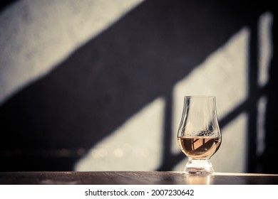 Image of a single malt whisky glass, with light and shadows in the background.