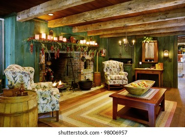 An image of a sitting room and fireplace in a primitive colonial style reproduction home.  The home is built with materials reclaimed from structures built in the late 1700's.