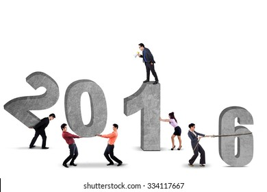 Image of six young businesspeople work together to arrange numbers 2016. Isolated on white background