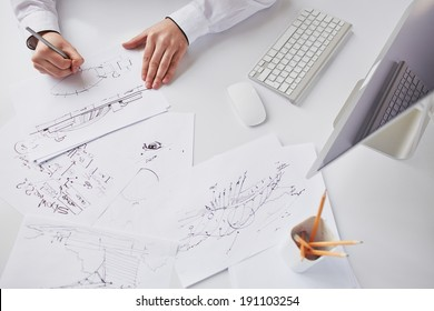 Image of sketches at workplace being drawn by businessman