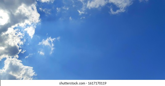 An image of a sky with some clouds on the left side of the picture but the right side was exposed.  In which the sun shines through the gap of the clouds down and is the sky at midday of winter.