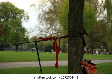 Image of a slack line tensioned between two trees in a green park.  Focus is on the tensioning mechanism.