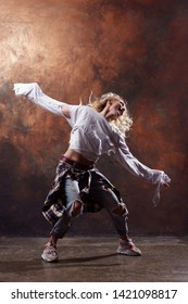 Image of slender blonde dancer with developing hair in torn jeans and sneakers on dark brown background