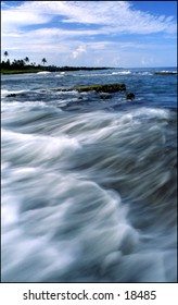 The Image is of a small Caribbean island with wave crashing on the rocky shoreline.  Using a slow shutter speed pleasantly blurs the waves.