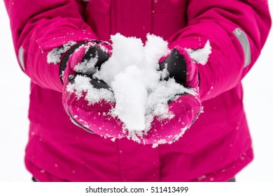 Image of a small child who holds in his hands a lump of snow.