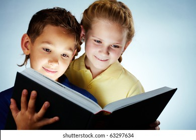 Image of smart children reading interesting book