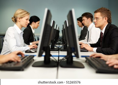 Image of smart people sitting at the tables at computer class
