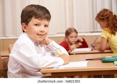 Image of smart schoolboy sitting at desk and looking at camera during lesson