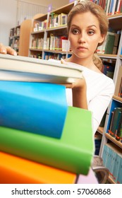 Image of smart student putting books in stack
