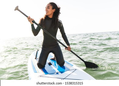Image of smiling african american woman in wetsuit working out with stand up paddle board on water