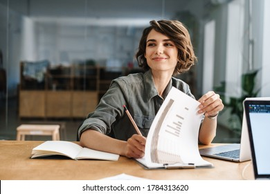 Image of smiling beautiful woman writing down notes while sitting at table in office - Shutterstock ID 1784313620