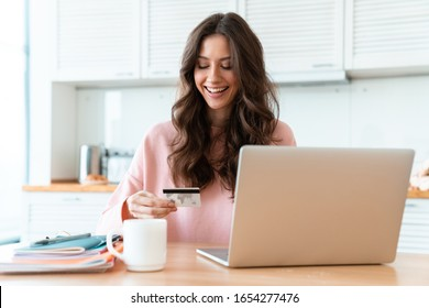 Image of a smiling cheerful beautiful young woman sit indoors at home using laptop computer holding credit card.
