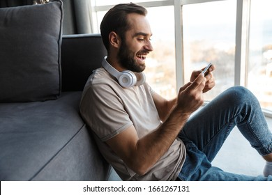 Image of a smiling cheery young man indoors at home play games by mobile phone sit on floor.