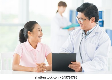 Image of a smiling doctor consulting his older patient on the foreground