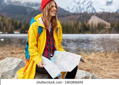 Image of smiling European female traveler with tourist map, searches for route in mountainious place, enjoys hiking, wears yellow raincoat and red headgear. Travel, camping and recreation concept