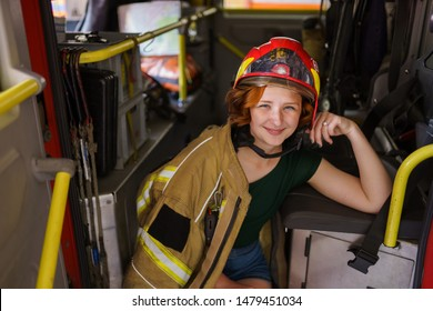 Image of smiling ginger firewoman looking in camera sitting in cab of fire engine