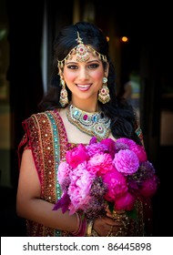 Image of a smiling Indian bride holding bouquet