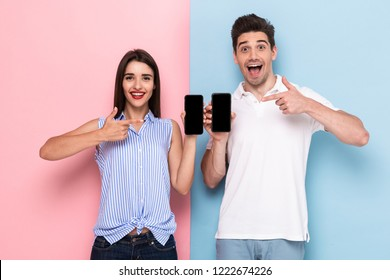 Image of smiling man and woman in casual wear standing and holding cell phones isolated over colorful background