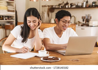 Image of smiling multicultural couple making notes in planner and using laptop in cozy kitchen