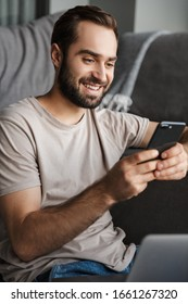 Image of a smiling positive young man indoors at home on sofa using laptop computer chatting by mobile phone.