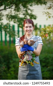 Image of smiling woman with beetroot in garden