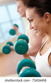 Image of smiling woman and guy doing lifting exercise with barbells in hands