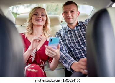 Image of smiling woman and man with phone in hands sitting in back seat of car .