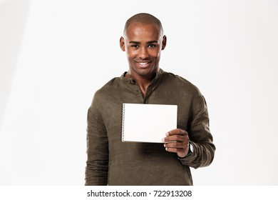 Image of smiling young african man standing isolated over white background. Writing notes looking camera showing notebook.