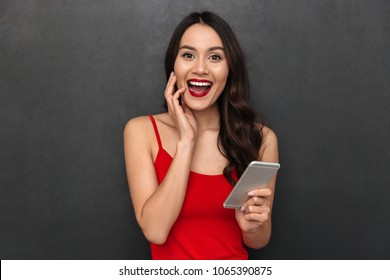 Image of smiling young asian woman standing isolated over dark grey wall background looking camera chatting by smartphone.