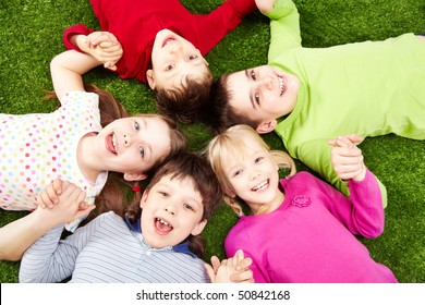 Image of smiling young boys and girls playing on the grass