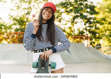 Image of smiling young girl wearing eyeglasses poising with skateboard and lollipop in skate park
