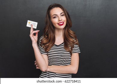 Image of smiling young lady standing over grey wall and holding debit card in hands. Looking at camera.