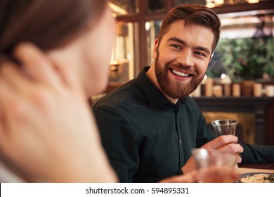 Image of smiling young loving couple sitting in cafe and eating. Looking at each other.
