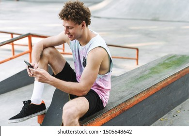 Image of smiling young man in streetwear sitting with skateboard and typing on cellphone at summer skate park