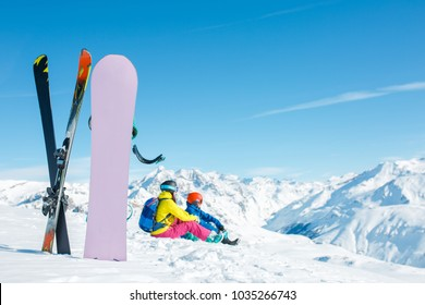 Image of snowboard, ski on background of sitting sports couple on snowy hill in winter afternoon